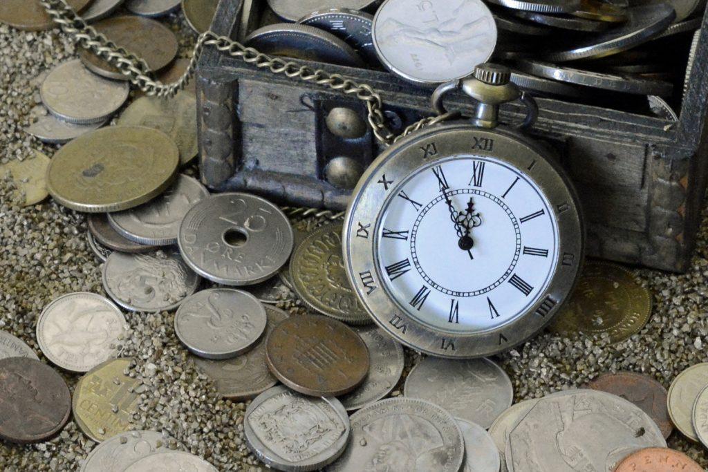 Une montre à gousset avec de vieilles pièces de monnaie dans des graviers dedans et en dehors d'un petit coffre.